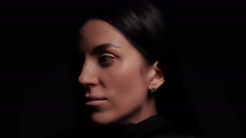 Female Face On A Black Background. Appears And Plunges Into Darkness Again