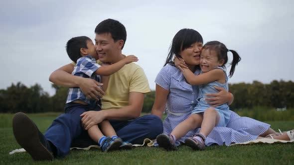 Thumbnail for Happy Asian Parents Embracing Their Joyful Kids