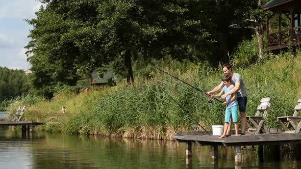 Father Teaching Son To Fish at Freshwater Pond