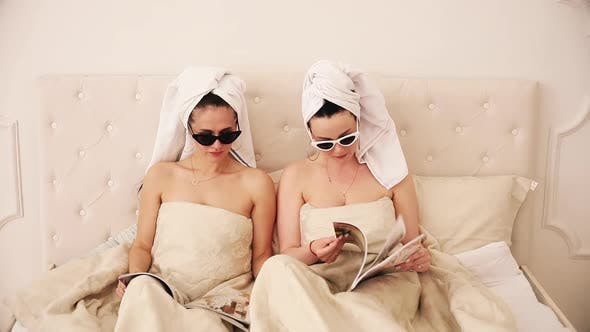 Cover Image for Two Beautiful Girls Lie on a Bed Under the White Blanket, Read Magazines and Surprised By Something