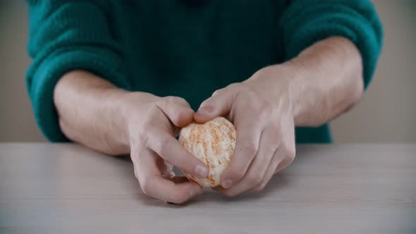 Thumbnail for A Man Is Breaking in Half an Orange
