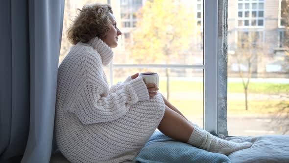 Thumbnail for Einsame Frau sitzt am Fenster mit Tasse