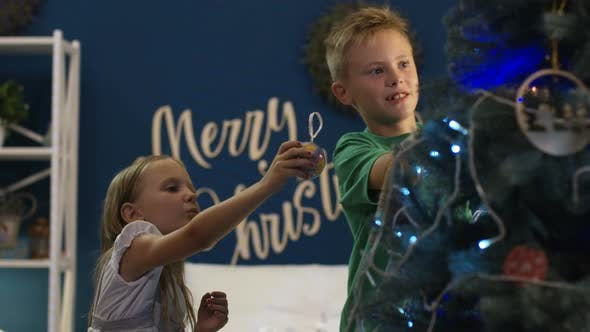 Cover Image for Siblings Decorating Spruce Christmas Tree