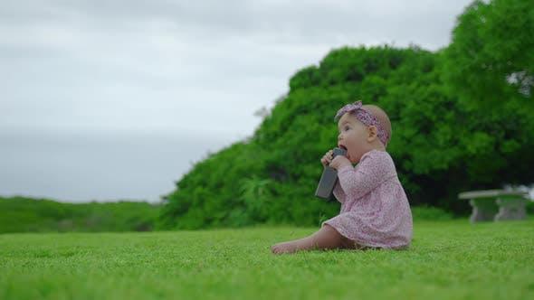Porträt eines entzückenden 6-monatigen Mädchens, das schwarzes Smartphone im Freien kaut und saugt