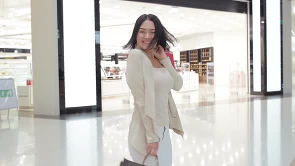 Happy young woman spins around with her shopping bags at mall