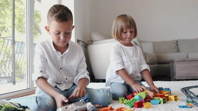 Brother and Sister Playing with Lego on Floor at Home