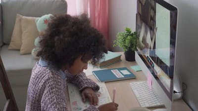 African School Kid Girl Online Learning with Remote Teacher at Home on Computer