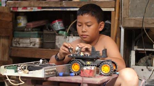 Asian Boy Creating Robotics Project