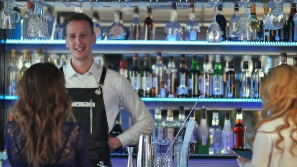 Thumbnail for Handsome bartender serving cocktail to beautiful woman
