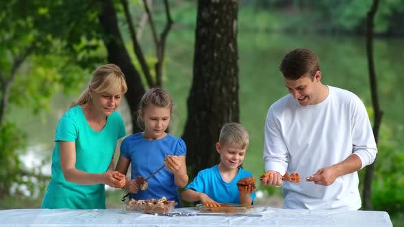 Dad, mom and kids put pickled meat on skewers. Family picnic in the Park.