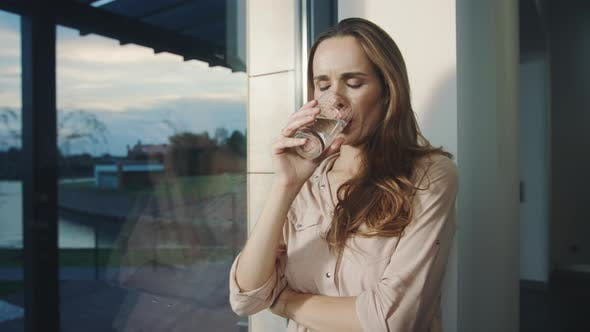 Thumbnail for Relaxed Woman Drinking Water Near Panoramic Window. Thirsty Lady Drinking Water