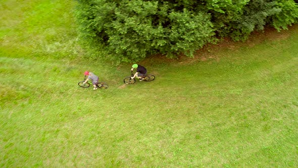 Thumbnail for Aerial view of man and woman cycling on dirt road in the summertime.