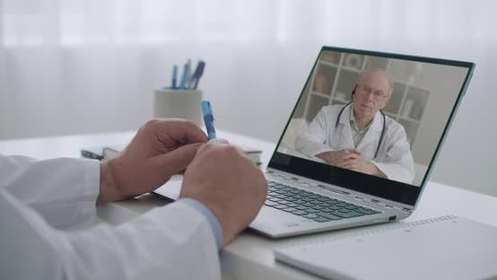 Cover Image for Two Therapists Are Consulting Online To Each Other By Videoconference From Their Offices in Clinics