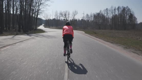 Woman cycling. Pedalling on bicycle. Female triathlete in helmet rides on bike. Cycling concept