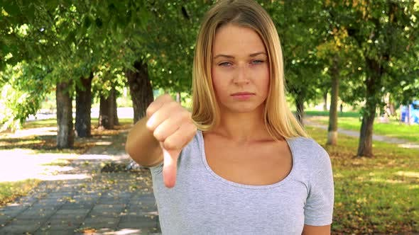 Thumbnail for Young Pretty Blond Woman Disagrees (Show Thumb Down) - Park with Trees in Background