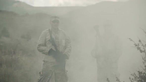 Thumbnail for Zwei Soldaten stehen in einer ableitenden Rauchwolke.