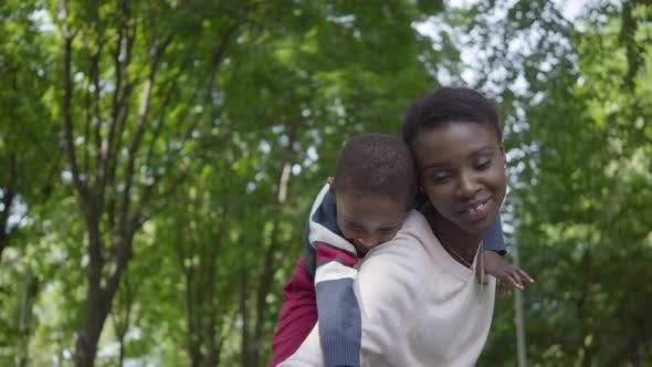 Thumbnail for Portrait of Cute African American Woman Holding Son on Her Back in the Green Park with Arms Spread