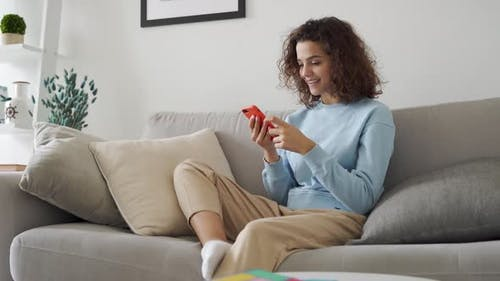 Happy Hispanic Teen Girl Holding Cell Phone Using Smartphone at Home