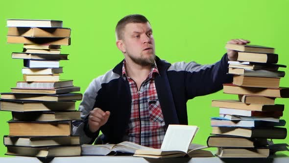 Thumbnail for Man Chooses the Most Interesting Book, and Writes in a Notebook. Green Screen