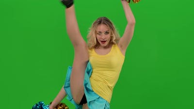 A Cheerleader Dances a Fiery Cheerleader Dance with Pompoms in the Studio on a Green Screen