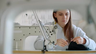 Two Young Dressmaker Working with Fabric in Design Bureau