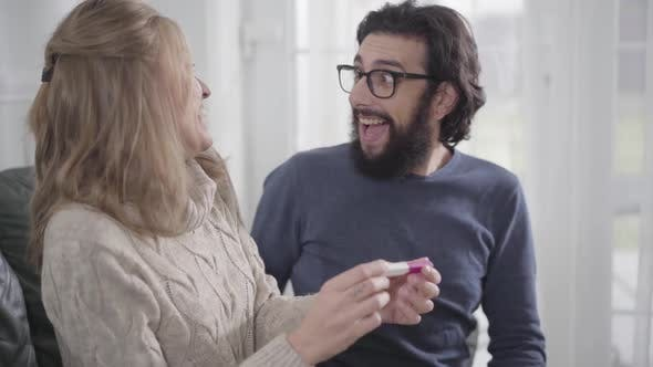 Thumbnail for Adult Caucasian Man in Eyeglasses Looking at Affirmative Pregnancy Test, Smiling and Hugging