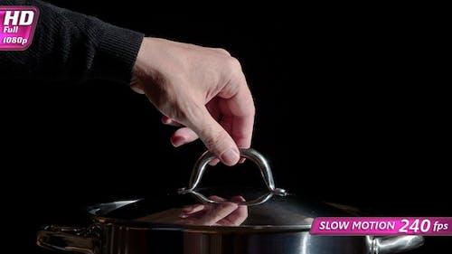 Koch nimmt den Deckel aus der Pfanne auf