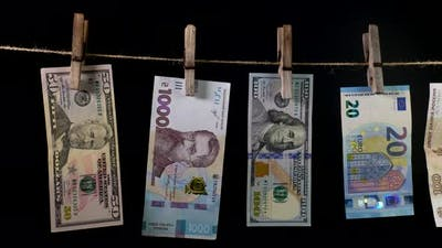 Banknotes of Different Countries Dry on a Clothespin Rope