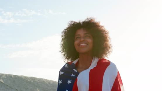 Cover Image for Woman wrapped with american flag and standing on beach