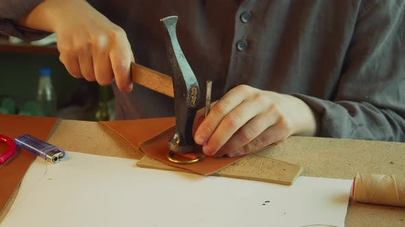 Thumbnail for Close-up Slowmotion Without a Face a Tailor with a Core and a Hammer Makes Holes in a Product Made