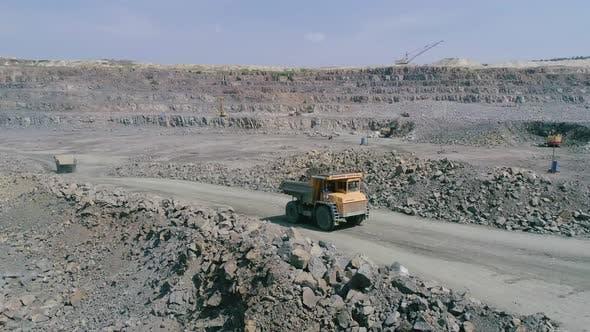 Thumbnail for Mining Dump Trucks in Large Granite Open Pit Mine. Loaded Truck Rides on Road Quarry Ledge Aerial