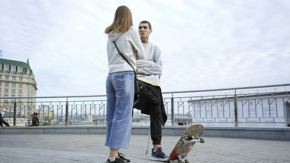Thumbnail for Young Man with One Leg on Crutches with Skateboard Talking with His Girlfriend on the Street