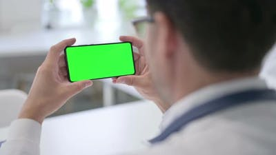 Doctor Holding Smartphone with Green Chroma Key Screen