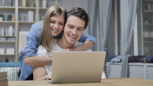 Thumbnail for Casual Happy Young Couple Using Laptop at Home