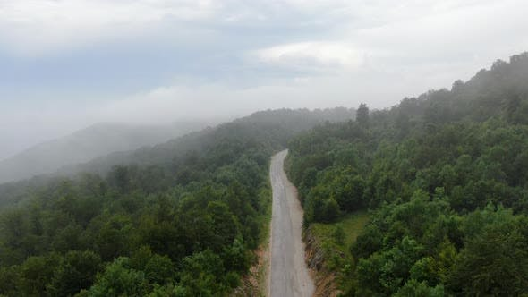 Thumbnail for Reverse Aerial Flight Through the Fog Above the Mountain Road