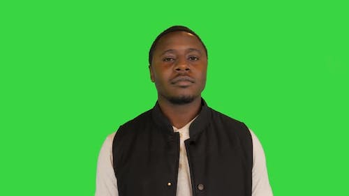 Happy African American Man Putting His Sunglasses on and Smiling on a Green Screen Chroma Key