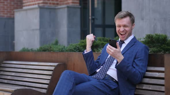 Thumbnail for Excited Businessman Celebrating Success, while Using Smartphone