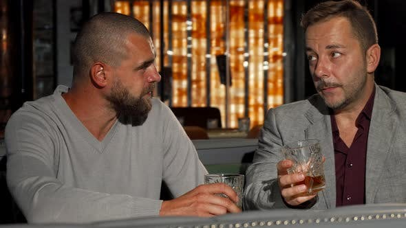Thumbnail for Two Male Friends Enjoying Whiskey at the Bar Together