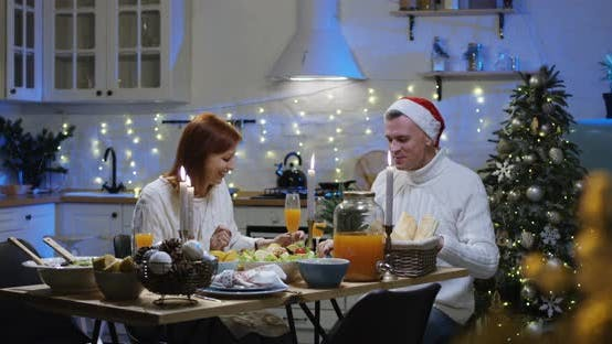 Thumbnail for Couple Talking and Eating at the Christmas Table