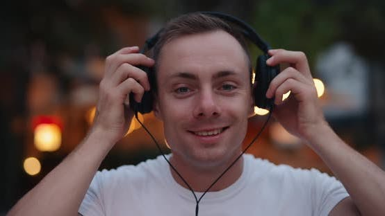 Smiling Man Puts on Big Headphones in the Evening City