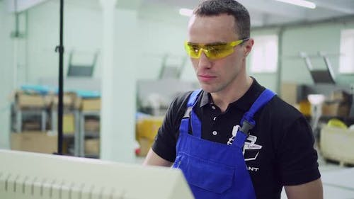 A Male Factory Worker is Standing at the Monitor
