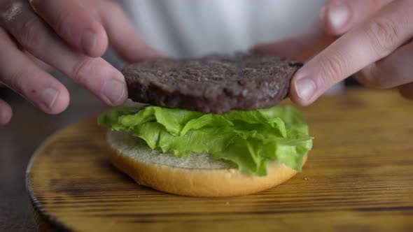 Thumbnail for Chef Cooks Burger and Puts Cutlet To the Leafs of Fresh Green Salad, Fast Food Restaurant, UHD 60p