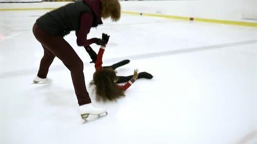 Professional Female Coach Training Girl on Ice Rink