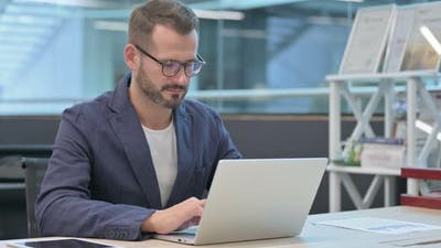 Middle Aged Businessman Working on Laptop in Office in Office
