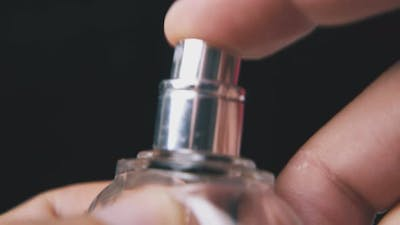 Man Sprays and Closes Perfume in Bottle on Dark Background