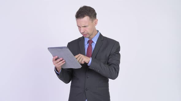 Cover Image for Studio Shot of Stressed Businessman Using Digital Tablet and Getting Bad News