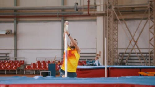 Pole Vaulting - Tall Sportsman in Yellow t Shirt Is Running and Jumping Over the Bar