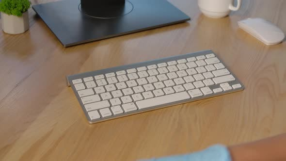 Hands in Protective Latex Gloves Sprays an Antiseptic on the Keyboard Surface and Thoroughly Cleanse