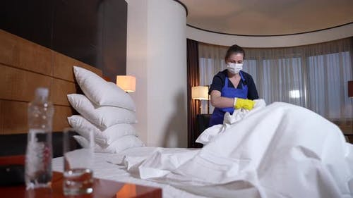 Hotel Staff in Protective Mask Removing Bedding
