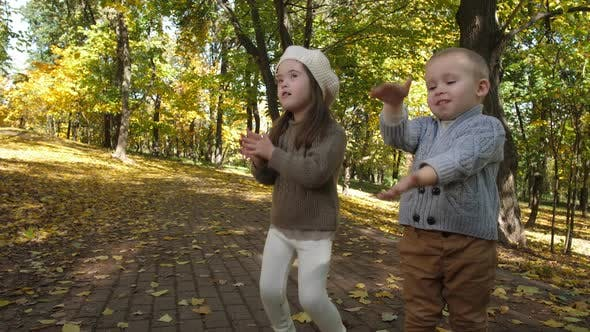 Cute Children Clapping and Singing in Autumn Park